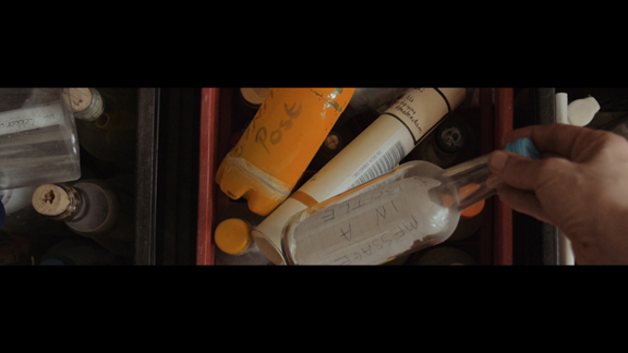 Still from Strophe showing messages in bottles
