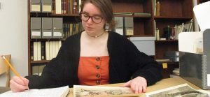 Photograph of curator Beck Moraski '21 sitting at a table in Special Collections reading room.