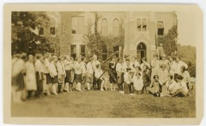 Photograph of a group of women on the lawn in front of a campus building. One woman is looking through a telescope.