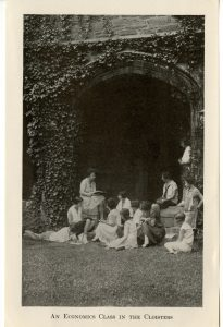 Photograph of students looking on, situated right near the ivy outside of the cloisters, as an instructor reads from an economics textbook.
