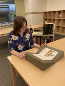 Student employee examines a book in our reading room. A cartful of books is behind her.
