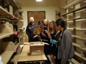 Catalogers and student employees, in processing room, hold up the last book above a shipping box.