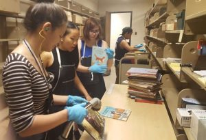 Student employees vacuum and shelve incoming books