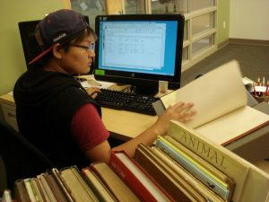 Student employee looks at one book while seated at a computer. A cart of books in the foreground.