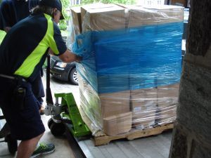 Delivery worker dragging a pallet of 45 large boxes onto a dolly